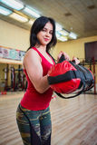 Woman training biceps muscle with heavy bag Royalty Free Stock Photos
