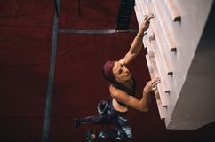 Woman training on a campus board. Woman practicing wall climbing on a campus board. Woman climbing on a campus board at a wall climbing gym Royalty Free Stock Images