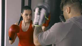 Woman training with coach in boxing club. Young woman training with coach in boxing club stock footage