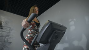 Woman training on a cross trainer in the gym. Happy brunette slim physique stock video footage