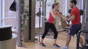 Woman training on crossover with coach. In gym. Young girl training in gym stock footage