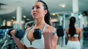 Woman training with dumbbells in hands in gym. Woman holding dumbbells in her hands. A girl trains the muscles of the arms. The woman at the same time bending stock video footage