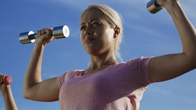 Woman training with dumbbells in sunlight. From below view of serious blond woman doing exercise for shoulder muscles with metal dumbbells standing outside in stock video footage