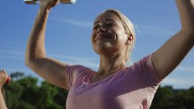 Woman training with dumbbells in sunlight. From below view of serious blond woman doing exercise for shoulder muscles with metal dumbbells standing outside in stock video