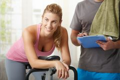 Woman training on exercise bike stock photos