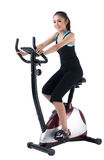 A woman training on exercise bike Stock Photos