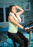 Woman training on exercise bike against pool Royalty Free Stock Images
