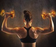 Woman training with  fiery dumbbells Royalty Free Stock Photography