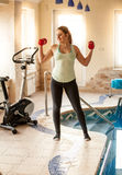 Woman training in fitness club with dumbbells Stock Photography