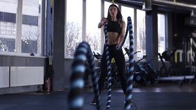 Woman training in gym with battle ropes. Powerful attractive caucasian woman do battle workout with ropes at the gym in stock footage