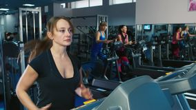 Attractive woman walking on a treadmill. Woman training in gym, cardio on the treadmill in the background train other visitors to the club stock video