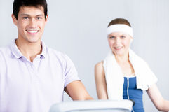 Woman training on gym equipment with coach in gym Royalty Free Stock Images