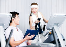 Woman training on gym training in gym with coach Royalty Free Stock Photography