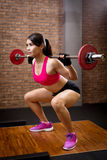 Woman with barbell. Woman training hard with barbell in the gym royalty free stock image