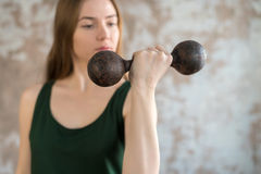 Woman training her biceps with an old dumbbell Royalty Free Stock Photography