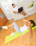 Woman training on mat and  boyfriend resting. Young women training on mat and  boyfriend resting at living room Stock Image