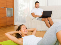 Woman training on mat and inert guy resting Royalty Free Stock Photos