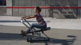 Woman training outdoor on exercise machine. Fitness woman doing exercises on training apparatus on city street stock video footage