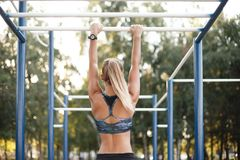 Woman training outdoors. Back view of fit tanned woman training outdoors on monkey bars. Athletic woman using outdoor exercise equipment for sports training Stock Image