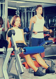 Woman training quadriceps muscles. Young women training quadriceps muscles using leg extension machinery in gym Royalty Free Stock Photography