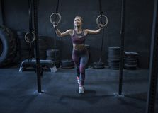 Woman training with rings. In crossfit room alone and happy Royalty Free Stock Photography