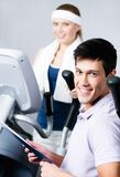 Woman training on simulators in gym with coach Royalty Free Stock Photos