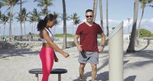 Woman training sportive man on beach stock video footage