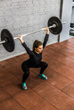 Woman training squats with barbells over head Royalty Free Stock Image