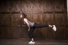 Sport concept - woman doing sports. Woman in training uniform and white sneakers diong sport in gym Royalty Free Stock Images
