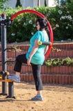 Woman training on a waist back massage machine Royalty Free Stock Photography