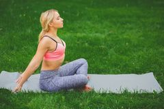 Woman training yoga in Bound Angle Pose . Fitness, woman training yoga in Bound Angle Pose outdoors in the park, copy space. Young slim girl makes exercise Royalty Free Stock Images
