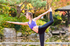 Woman training yoga outdoor in autumn Stock Image