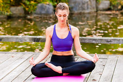 Woman training yoga outdoor in autumn Stock Photography