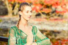 Woman training yoga outdoor in autumn park Royalty Free Stock Photography