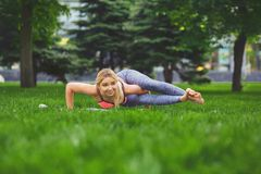 Woman training yoga pose outdoors. Fitness, woman training yoga pose outdoors in the park, copy space. Young slim girl makes exercise. Stretching, wellness Stock Image