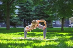 Woman training yoga pose outdoors. Fitness, woman training yoga pose outdoors in the park, copy space. Young slim girl makes exercise. Stretching, wellness Royalty Free Stock Images