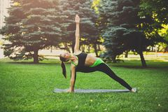 Woman training yoga pose outdoors. Fitness, woman training yoga pose outdoors in the park, copy space. Young slim girl makes exercise. Stretching, wellness Stock Photography