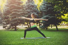 Woman training yoga pose outdoors. Fitness, woman training yoga pose outdoors in the park, copy space. Young slim girl makes exercise. Stretching, wellness Stock Images