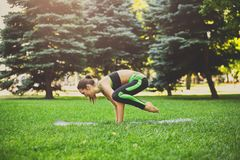 Woman training yoga pose outdoors. Fitness, woman training yoga pose outdoors in the park, copy space. Young slim girl making exercise. Stretching, wellness Stock Photography