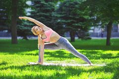 Woman training yoga pose outdoors. Fitness, woman training yoga pose outdoors in the park, copy space. Young slim girl makes exercise. Stretching, wellness Royalty Free Stock Image