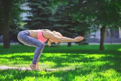 Woman training yoga pose outdoors. Fitness, woman training yoga pose outdoors in the park, copy space. Young slim girl makes exercise. Stretching, wellness Royalty Free Stock Photo