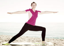 Woman training yoga poses on beach Royalty Free Stock Photos