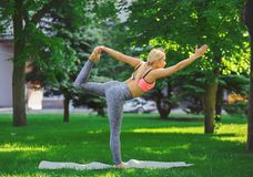 Woman training yoga in std bow pose. Fitness, woman training yoga in std bow pose outdoors in the park, copy space. Young slim girl makes exercise. Stretching royalty free stock photography