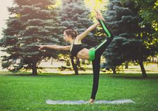 Woman training yoga in std bow pose. Fitness, woman training yoga in std bow pose outdoors in the park, copy space. Young slim girl makes exercise. Stretching stock photo