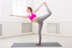 Woman training yoga in std bow pose. Fitness, woman training yoga in std bow pose in gym at white background, copy space. Young slim girl makes exercise stock image