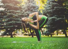 Woman training yoga in twisting awkward pose. Fitness, woman training yoga in twisting awkward pose outdoors in the park, copy space. Young slim girl makes Stock Images