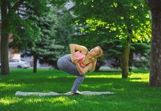 Woman training yoga in twisting awkward pose. Fitness, woman training yoga in twisting awkward pose outdoors in the park, copy space. Young slim girl makes Royalty Free Stock Images