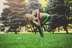 Woman training yoga in twisting awkward pose. Fitness, woman training yoga in twisting awkward pose outdoors in the park, copy space. Young slim girl makes Royalty Free Stock Photo