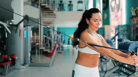 Woman trains abdominal muscles and arms in gym stock video footage