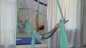 A woman trains on the air in the hall alone. A woman trains on the air in the hall alone gymnastics. Inventory is two long cloths of stretching or strong Air stock video